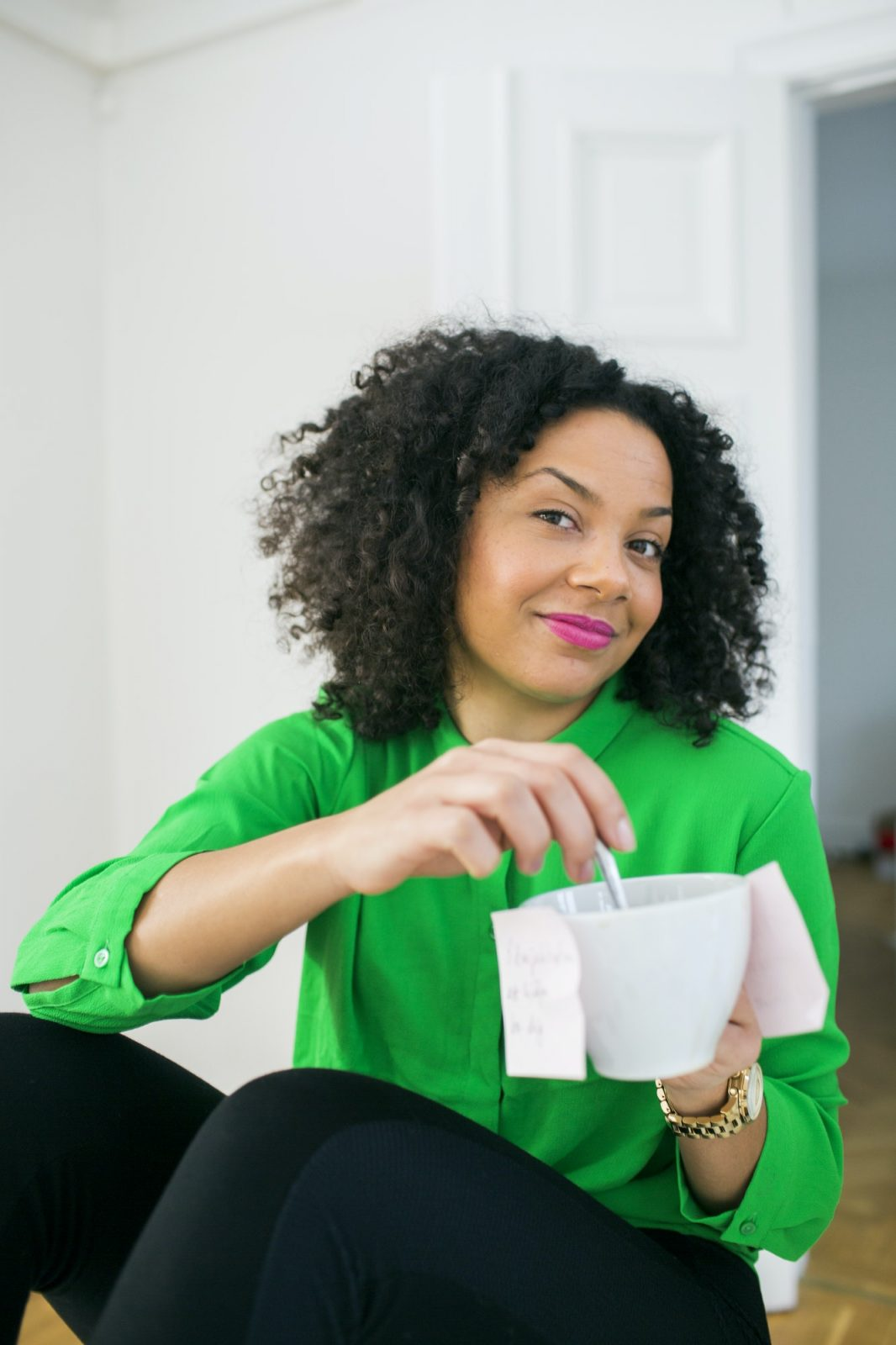 Portrait of young businesswoman with adhesive notes stuck on coffee cup in office